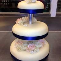 Bryllupskake med lilla sløyfe og marsipanblomster.